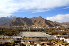 The panoramic view of Lhasa city, in front of Potala Palace and Palace square, with modern building and mountains, far away a Tib. Et Peaceful Liberation royalty free stock images