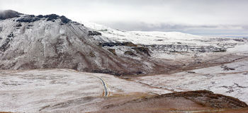 Panoramic view of light snowfall at Golden Gate as it covers the Drakensberg mountains on a cold morning. Royalty Free Stock Images