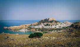 Panoramic view on Lindos town with a beautiful lagoon and ancient fortress on a hill at Rhodes island, Greece Stock Photos