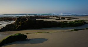 Panoramic view of linear rock formations exposed at low tide along Pacific Coast. A panoramic view of long, linear rock formations exposed and emerging at low royalty free stock image