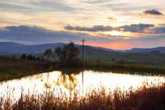 Panoramic view of a little pond, rolling hills, sky and clouds at sunset in tuscan countryside landscape, Tuscany, Italy. Europe Royalty Free Stock Image