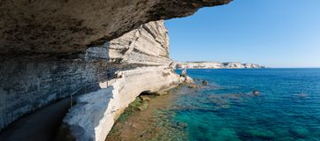 Panoramic view looking out from a coastal path cut into the side of a white limestone chalk cliff which leads to the King of Arago stock image