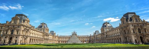 Panoramic view of the main courtyard of the Louvre palace with the historical buildings and the modern pyramid, Paris france. Panoramic view of the main Royalty Free Stock Photo
