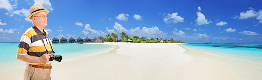 Panoramic view of a male tourist standing on a tropical beach at stock photography