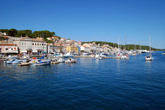 Panoramic view at Mali Losinj harbour,Croatia. Panoramic waterfront view on the houses, motorboats and yachts in Mali Losinj in a sunny summer day with blue sky Stock Photo