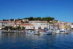 Panoramic view at Mali Losinj harbour,Croatia. Panoramic waterfront view on the houses, motorboats and yachts in Mali Losinj in a sunny summer day with blue sky Royalty Free Stock Image