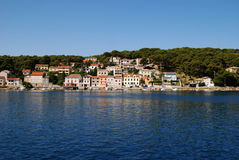 Panoramic view at Mali Losinj harbour,Croatia. Panoramic waterfront view on the houses and pine forest in Mali Losinj in a sunny summer day with blue sky Royalty Free Stock Photography