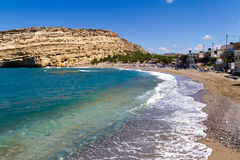 Panoramic view of Matala beach south Crete. Panoramic skyline view of Matala beach , Crete. Roman era graves cut into the sinking cliffs became the lodgings for Royalty Free Stock Photos