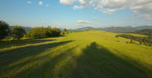 Panoramic view of a meadow and mountains Stock Image