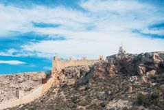Panoramic view of medieval moorish fortress Alcazaba in Almeria. Over the desert hill mountain and the statue of the Sacred Heart of Jesus staying on the hill Stock Image
