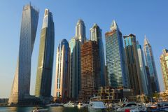 Panoramic view with modern skyscrapers and water pier of Dubai Marina at sunset, United Arab Emirates royalty free stock image