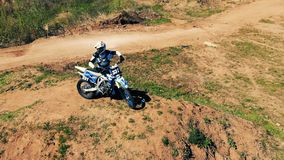 Panoramic view of a motorcyclist with his bike on a hill. Aerial epic shot. stock video footage
