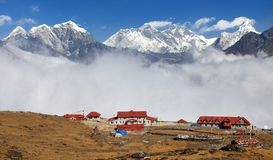 Panoramic view Mount Everest Lhotse and Ama Dablam from Kongde with tourist lodge and beautiful clouds, Sagarmatha national royalty free stock images