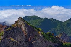 Panoramic view of mountain peaks against clouds below horizon and clear blue sky on sunny day. View from Pico do Arieiro on Portuguese island of Madeira royalty free stock image