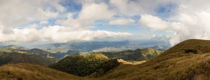 Panoramic view of mountain range coverd with brown grass and gre. Panoramic view of mountain range coverd with brown grass field and green tropical rain forest Royalty Free Stock Images