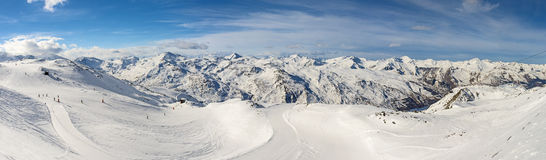 Panoramic view of mountain range with ski piste. Ski slope piste in winter alpine resort with european alps mountain range in background Royalty Free Stock Images