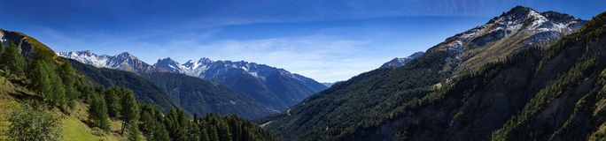 Panoramic view from mountain top. Spring in the alpine mountain range. View to the mountain peaks and a valley royalty free stock photos