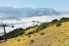 The panoramic view of Mountain Zugspitze from top of Mount Wank with a cable car gliding above sea of clouds in Garmisch Partenkir Stock Photos