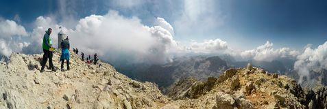 Panoramic view of Mountaineer expedition climbing to rocky mountain summit Triglav on Julian Alps. Mountain range royalty free stock image