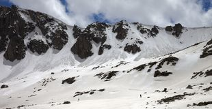 Panoramic view on mountains with snow cornice and avalanche trail. Panoramic view on high mountains with snow cornice and avalanche trail, snowy plateau and two stock images