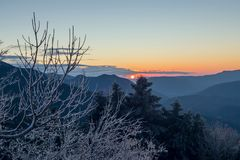 Panoramic view of the mountains. Winter landscape. Panoramic view of the mountains in the distance, a spruces and ice-covered trees on a winter evening at sunset Royalty Free Stock Image