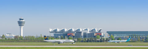Panoramic view of Munich international airport with taxiing airliner. Munich, Germany - May 6, 2016: Panoramic view of Munich international airport with taxiing Royalty Free Stock Photography