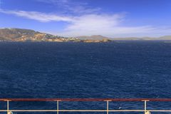 Panoramic view of Mykonos from cruise ship deck. Sea horizon in the wind: coast of Greece in the Aegean islands. Scenery of rocky coastline: azure waters of the stock photo