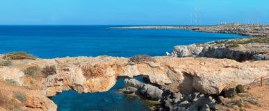 Panoramic view of a natural rock bridge at sea. Panoramic view of natural rock bridge at Cape Greco near Ayia Napa, Cyprus, Mediterranean Sea coast royalty free stock photography