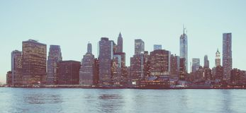 Panoramic view of New York Financial District and the Lower Manhattan at dawn viewed from the Brooklyn Bridge Park. Low contrast royalty free stock photos