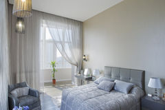Panoramic view of nice cozy bedroom. Nice cozy bedroom in luxury home Royalty Free Stock Image