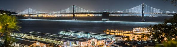 Panoramic view of the night illuminated Bay Bridge connecting San Francisco and Oakland; Ferry terminals and ptehr piers in the royalty free stock image