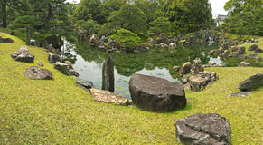 Panoramic view of Ninomaru Garden with ornamental stones in a la. Rge pond. Panorama of traditional Japanese garden during spring in Kyoto, Japan Stock Photo
