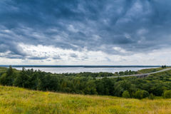 Panoramic view of North Dvina riverbank. North Dvina Riverbank with bridge, grass, forest Royalty Free Stock Image