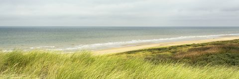 Panoramic view on the North Sea at te west coast of the Netherlands. Wide open landscape with water, sky, grass and horizon royalty free stock image
