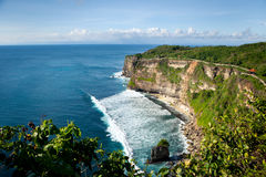 Panoramic view of the ocean with waves high cliff. Panoramic view of the ocean with waves with a high cliff on a Sunny day with clouds. Uluwatu, Bali Royalty Free Stock Image