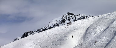 Panoramic view on off-piste slope with traces from skis and snow Royalty Free Stock Photo