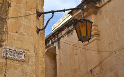 Panoramic view on a old, antic, medieval and historic lantern hanging on a sand stone wall. In the Background the castle of Mdina stock photos