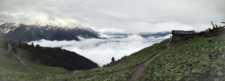 Panoramic view with an old farm house in foggy mountains Royalty Free Stock Photo