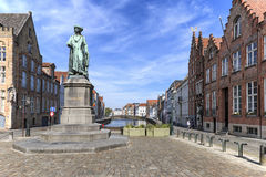 Panoramic view of the old streets of Bruges with a statue of Jan Van Eyck, a famous Flemish artist, on foreground Royalty Free Stock Image