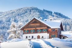 Traditional farmhouse in winter wonderland in the Alps. Panoramic view of old traditional farmhouse sitting on top of a hill in scenic winter wonderland scenery Stock Image
