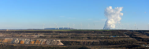Panoramic view open cast mining, power plant and wind energy. Changing from dirty coal energy to clean wind energie Stock Images