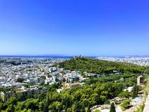 Panoramic View over Athens, Greece. Sunny day`s panoramic view over the city scape of the Athens in Greece. Green park, white city structures and blue sky and royalty free stock images