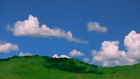 Panoramic view over the green valley with blue sky and white clo Stock Image