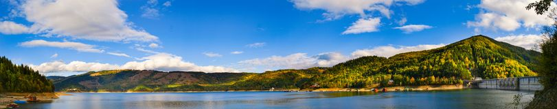 Panoramic view over Izvorul Muntelui lake and dam. With autumn scenery and beautiful blue sky Royalty Free Stock Photos