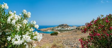 Panoramic view over Lindos village with ruins of ancient Acropolis. Island of Rhodes. Greece. Europe. Panoramic, distant view at Lindos village with ruins of stock image