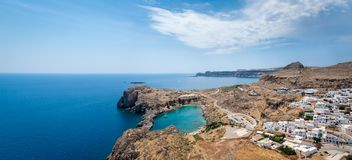 Panoramic view over Lindos village with ruins of ancient Acropolis. Island of Rhodes. Greece. Europe. Panoramic view over Lindos village with Saint Paul`s Bay stock photos