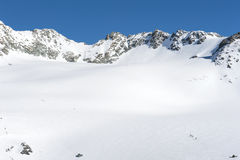 Panoramic view over a snowy slope with hikers Royalty Free Stock Photo