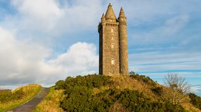 Panorama of a path leading to an old hilltop castle tower under a blue sky with white puffy clouds royalty free stock photography