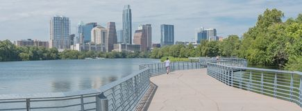 Panoramic view people enjoy outdoor activities on boardwalk in d. Panorama view people biking running walking along boardwalk near downtown Austin, Texas in royalty free stock photos