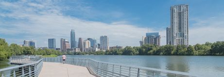 Panoramic view people enjoy outdoor activities on boardwalk in d. Panorama view people biking running walking along boardwalk near downtown Austin, Texas in royalty free stock photography